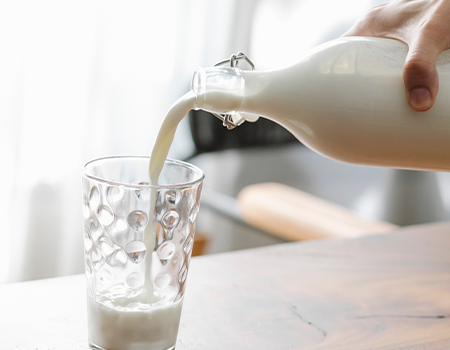 Pouring milk in a glass from a bottle