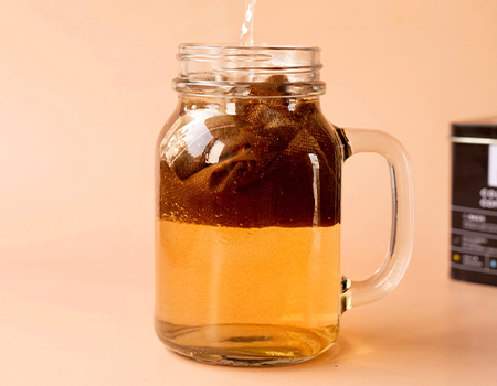 A jar with Rage Cold Brew coffee bag and water