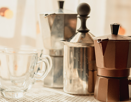 Different sizes of Moka Pot kept together along with a milk frother