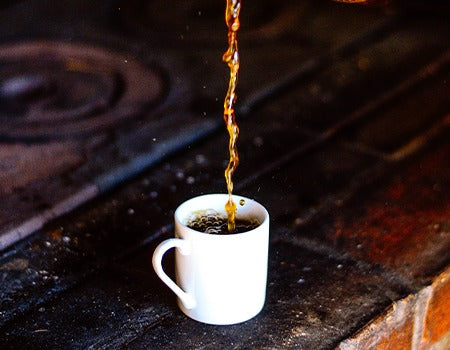 Adding filtered coffee to a cup