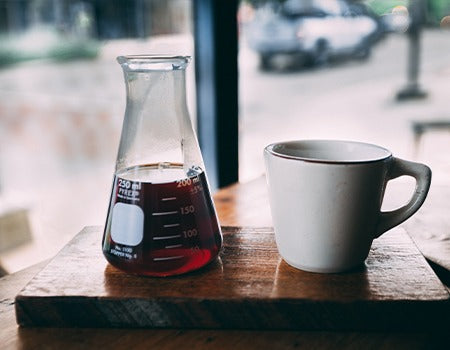 Tall flask filled with freshly brewed coffee