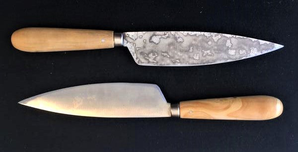 two carbon steel knives on a black granite cutting surface