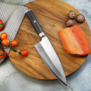 356mm German stainless steel deba knife laying on a round wood cutting board with salmon and vegetables