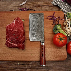 Masuta Knife Imports Gamma Cleaver knife laying on a bamboo cutting board with a large piece of raw beef and some vegetables