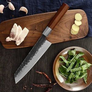 carbon steel kiritsuke knife next to a cutting board with chicken, potatoes, garlic, and herbs prepared for display