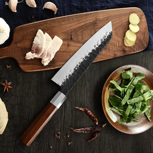carbon steel kiritsuke knife laying over a cutting board with prepared veggies and meats