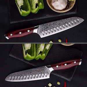297mm santoku knife on display on a black granite cutting surface with green onions and garlic