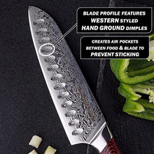 Load image into Gallery viewer, Showcasing the damascus blade core and blade profile dimples over a black cutting board with prepped vegetables