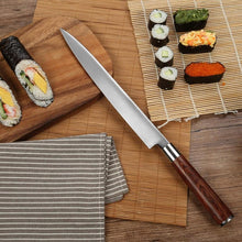 Load image into Gallery viewer, Yanagiba knife leaning on a wooden cutting board among different pieces of sushi and and a sushi rolling mat