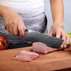 Professional chef holding Masuta damascus nakiri knife while cutting fish and vegetables on a wood cutting board