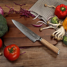 Load image into Gallery viewer, Carbon steel damascus santoku blade leaning on a dark wood cutting board with tomatoes mushrooms and broccoli