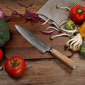 Carbon steel damascus santoku blade leaning on a dark wood cutting board with tomatoes mushrooms and broccoli