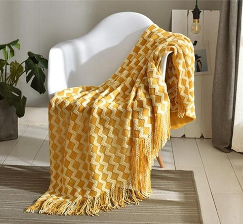 Photograph of a mustard coloured wavy designed throw kept on a white chair