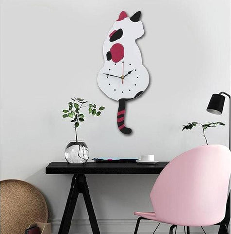 A wall clock in shape of a cat white in colour