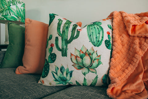 Photograph of a cacti cushion with orange coloured throw