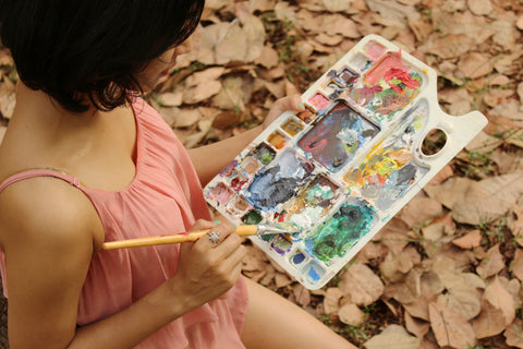 Photograph of a girl holding a brush and a colour palette tray