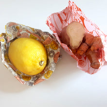 Load image into Gallery viewer, two snack size wax wraps, one holding a lemon, the other holding ginger root