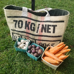 upcycled tote bag with cartons of fresh vegetables in front on bright green grass