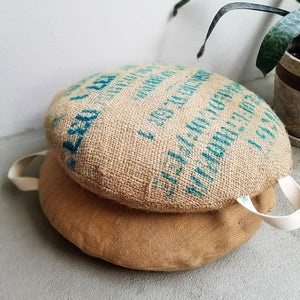 Upcycled coffee sack floor pillows, two stacked in the foreground with a plant in the background