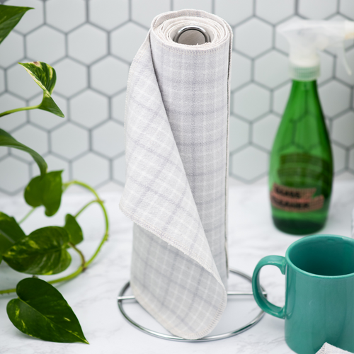 a spool of light grey plaid paperless towels stands upright in the centre with a leafy green plant on the left, and a green glass spray bottle and teal mug on the right