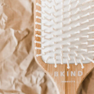 Close up view of bamboo hair brush bristles on top of crumpled brown paper