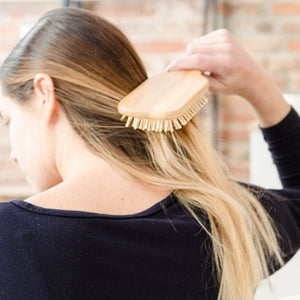 Back 3/4 view of a caucasian woman brushing her long blonde hair with a bamboo hair brush. There is a brick wall in the background and the back of a wooden chair in the foreground.