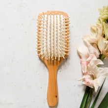 Load image into Gallery viewer, A bamboo hair brush lies face up next to some cut flowers