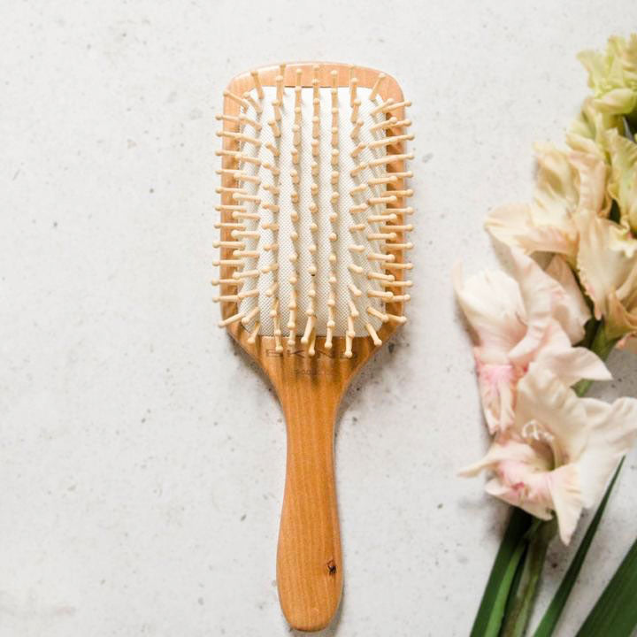 A bamboo hair brush lies face up next to some cut flowers
