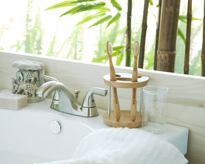 Two Brush with Bamboo adult toothbrushes in a wooden holder on the edge of a bathroom sink