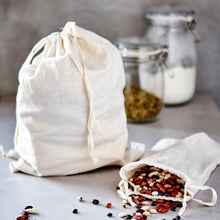 Load image into Gallery viewer, two natural cotton bulk bags are in the foreground; one standing up and full, the other tipped over and spilling dried beans. two half full glass jars are in the background