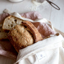 Load image into Gallery viewer, Dans Le Sac natural cotton bread bag with a baguette sticking out, there is flour and a measuring cup in the background
