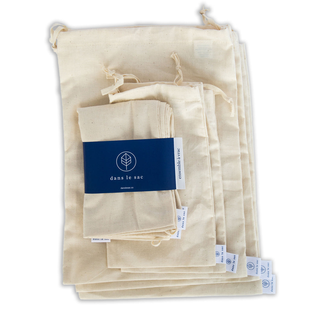 Set of 5 natural cotton bulk bags stacked with another set on top, packaged with navy blue paper