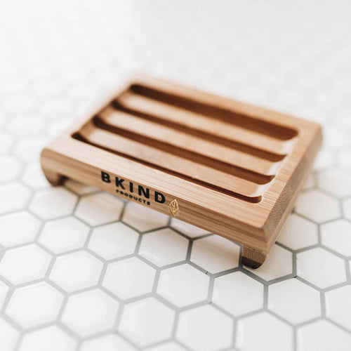 A rectangular bamboo soap dish with drainage slots sits on a tiled surface