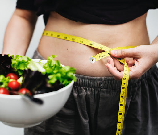Person holding bowl of salad with measure tape around waist, for AutoBrush blog