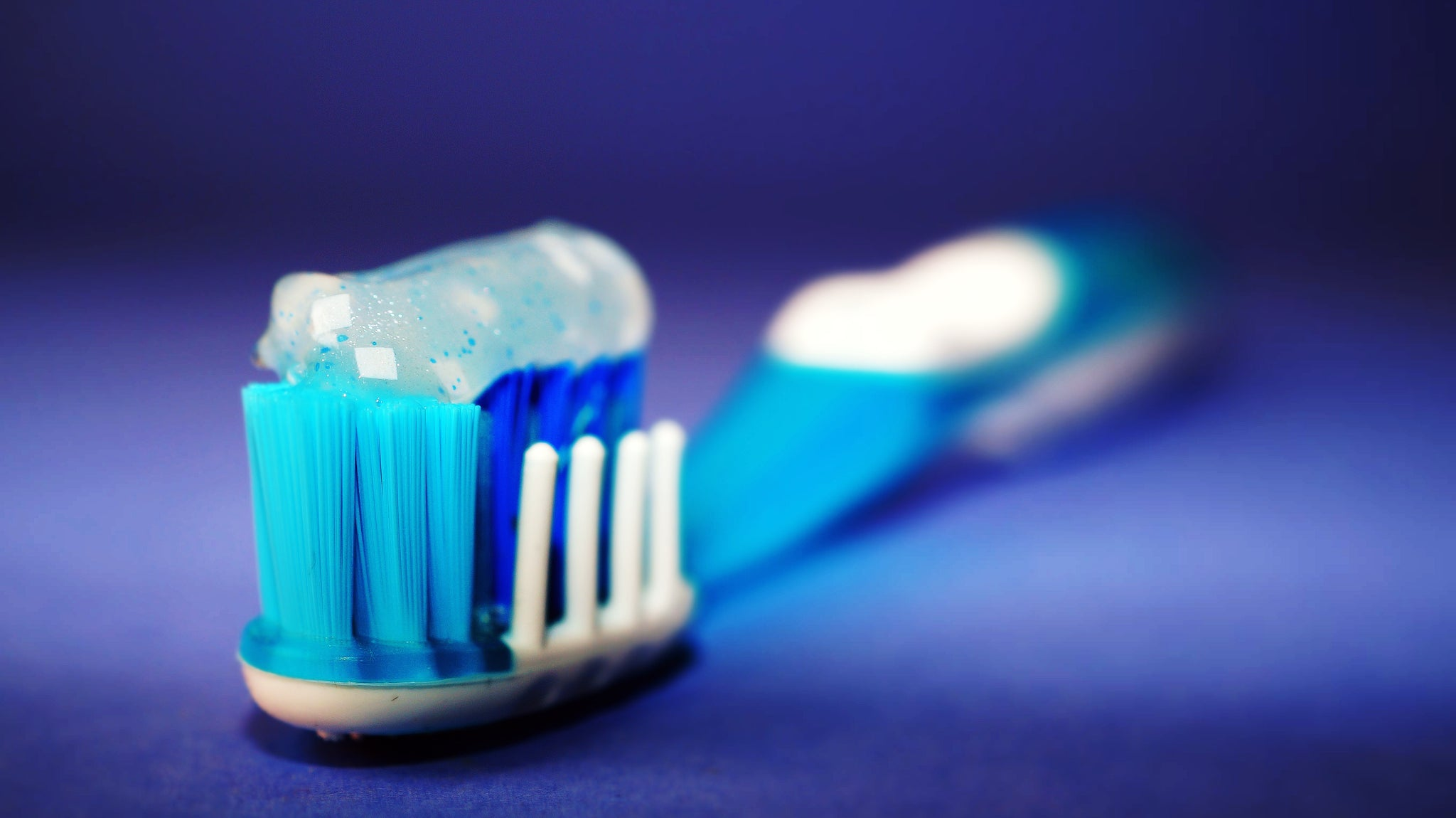 Blue and white bristled toothbrush with toothpaste on, for AutoBrush