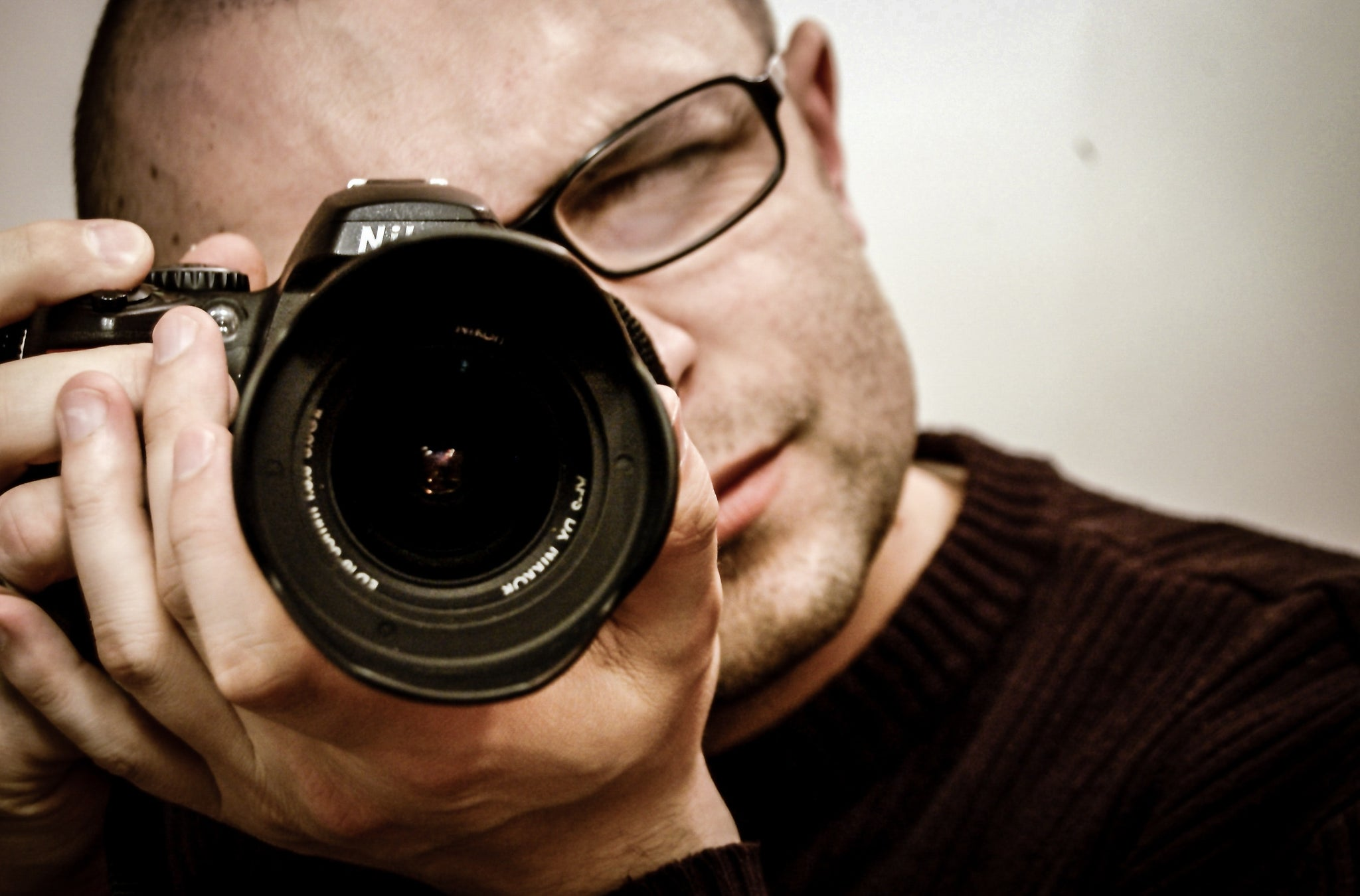 Man wearing glasses pointing a camera, for AutoBrush