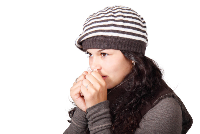 Woman wearing a beanie with her hands close to her mouth, for AutoBrush
