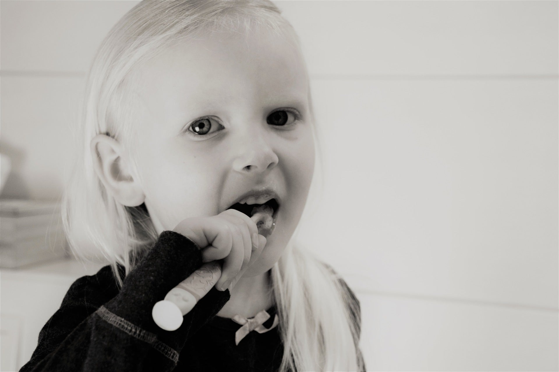 Black and white image of blonde little girl brushing her teeth, for AutoBrush
