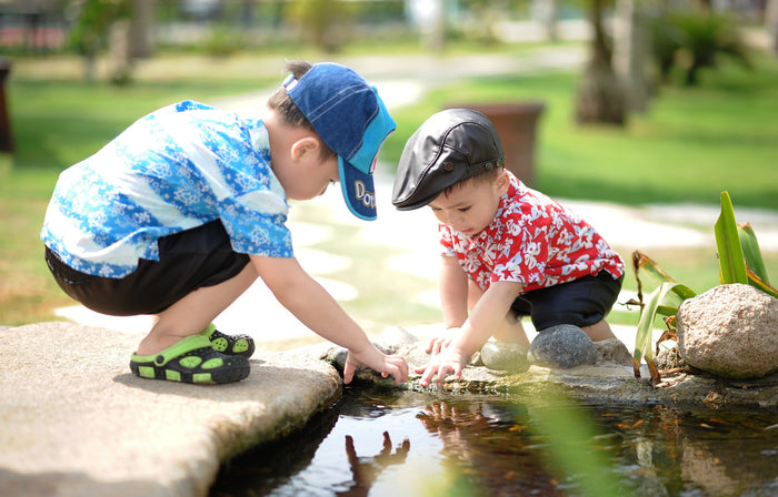 Two kids wearing hats, playing near a pond, for AutoBrush