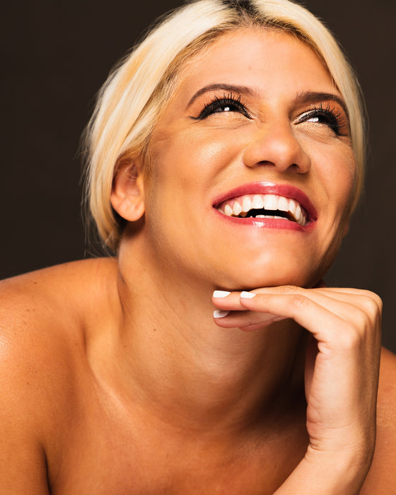 Blonde woman smiling while looking upward, for Autobrush