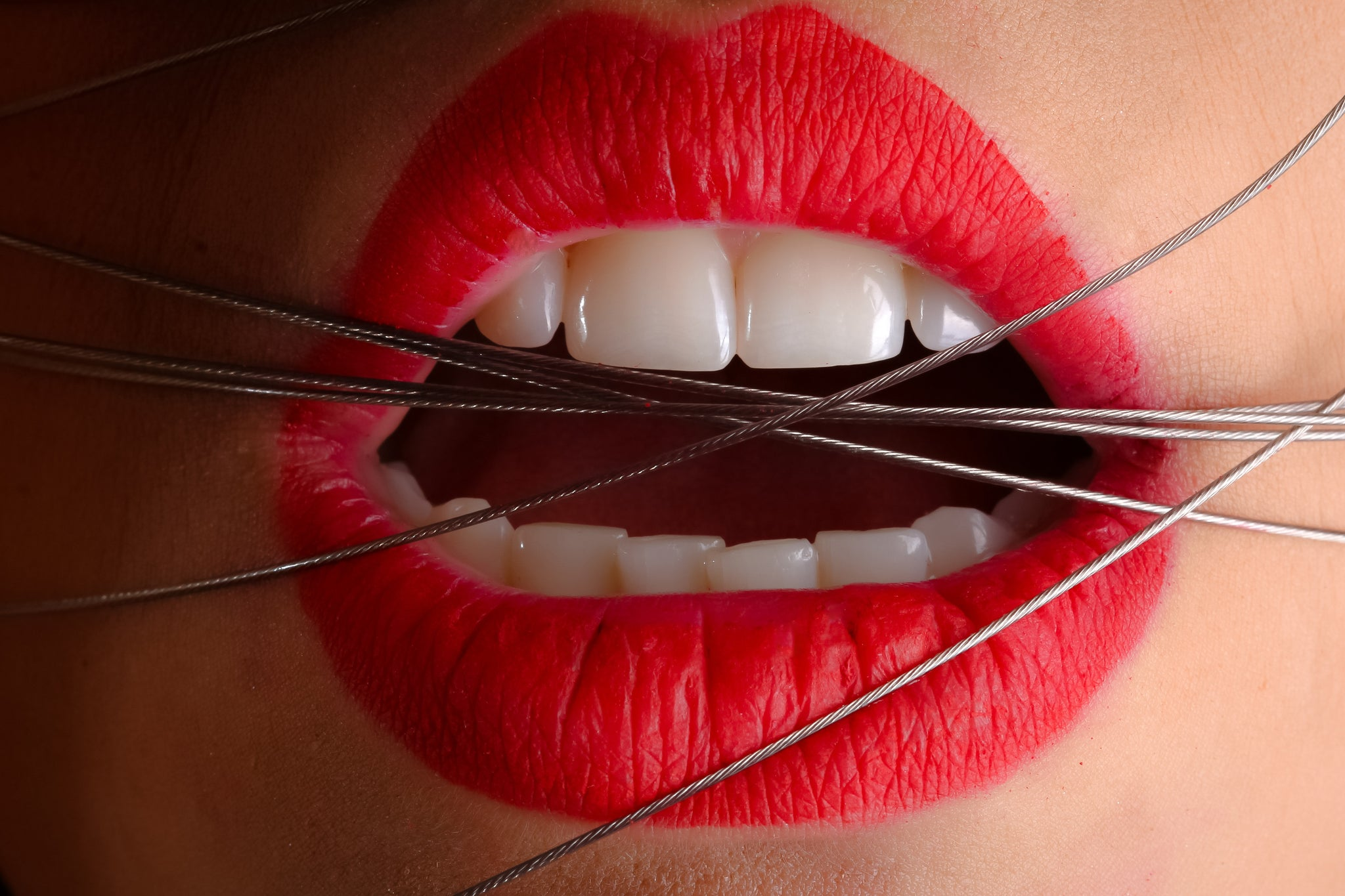 Woman with red lipstick with wires wrapped around her mouth, for AutoBrush