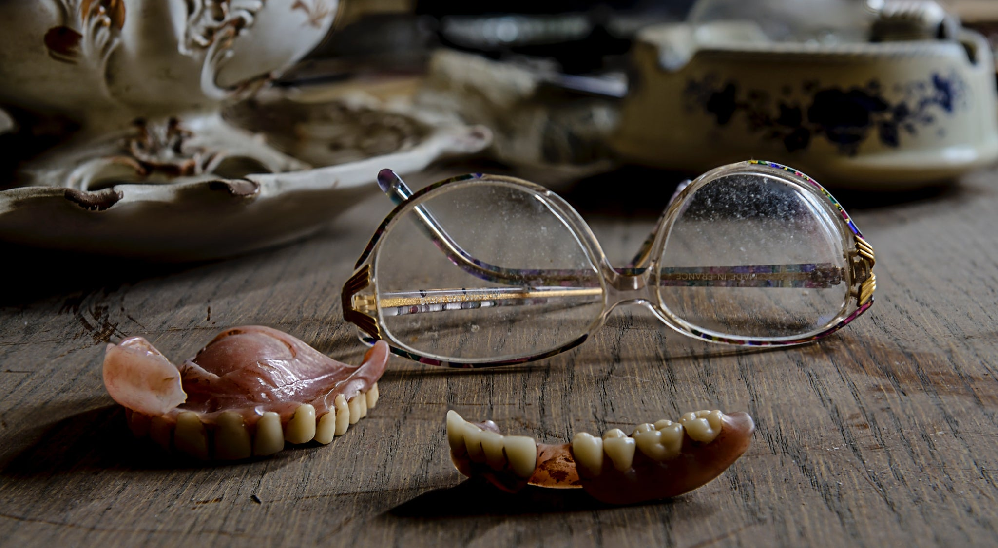 Reading glasses and a pair of dentures on top of a wooden table, for AutoBrush