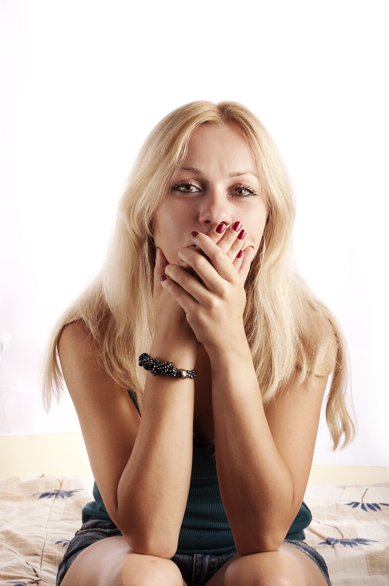 Blonde woman with her hands over her mouth, for AutoBrush