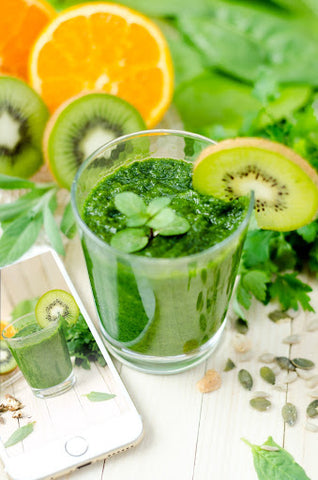 Glass of juice surrounded by oranges and kiwi, for AutoBrush blog