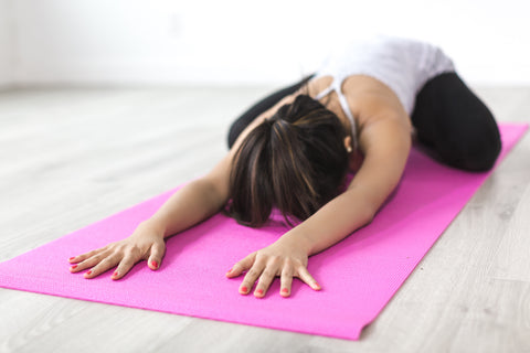 Woman stretching her arms across the pink yoga mat, for AutoBrush