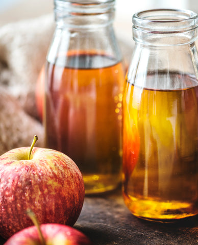 Two bottles of apple cider vinegar and two apples, for Autobrush