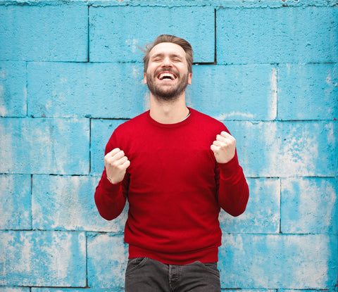 A happy man wearing red sweatshirt on a blue brick background, for AutoBrush