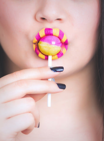 Women eating lollipop with same colors on lips, for AutoBrush