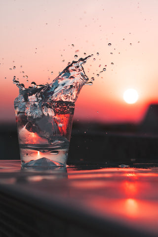 Glass of splashing water with a sunset in the background, for Autobrush