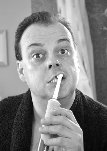 Black and white image of a man brushing his teeth, for AutoBrush